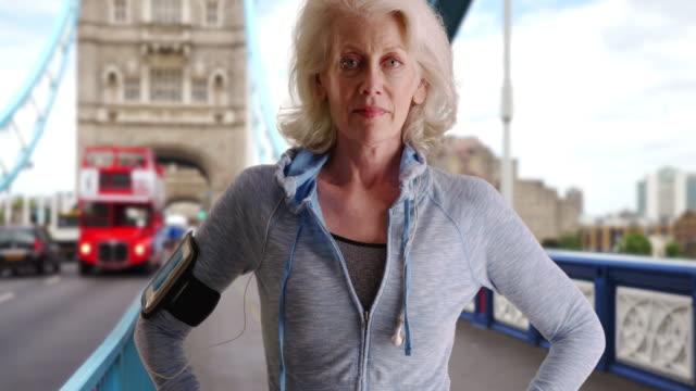 stockvideo's en b-roll-footage met mature female runner on the tower bridge posing for portrait - jogster