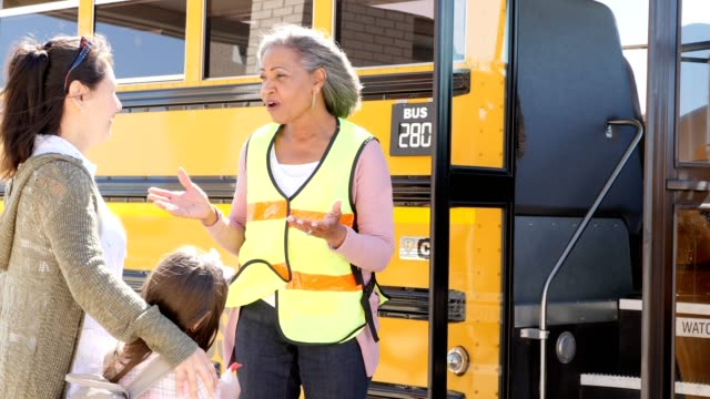 mature female school bus driver reassures a child's mom before the mom's daughter gets on the school bus - bus driver stock videos & royalty-free footage