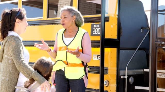 vídeos y material grabado en eventos de stock de el conductor de autobús escolar maduro tranquiliza a la madre de un niño antes de que la hija de la madre se ponga en el autobús escolar - adios
