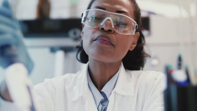 vidéos et rushes de mature female scientist doing experiment at laboratory - lunettes de protection