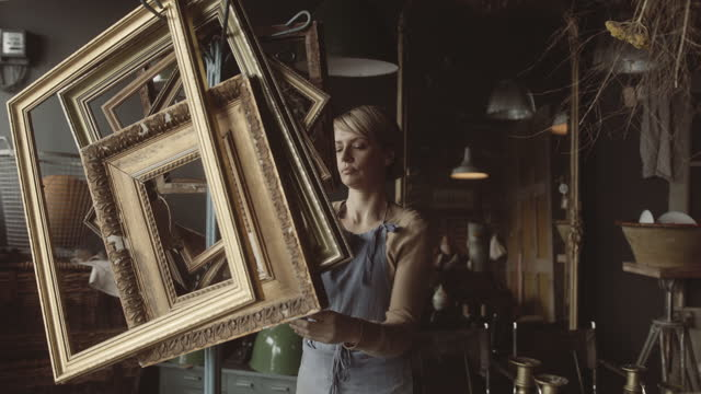 mature female shop owner working in antique store arranging picture frames - small stock videos & royalty-free footage