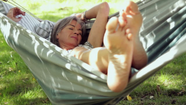 vidéos et rushes de ms mature female sleeping in hammock / london, united kingdom - hamac