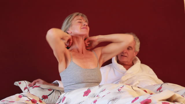 Mature female stretching in bed