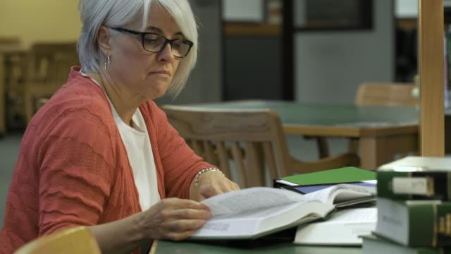 vídeos de stock e filmes b-roll de mature female student working in college library. - óculos de leitura