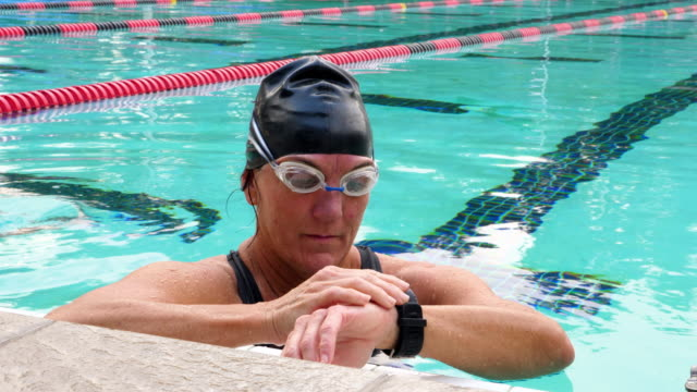 ms mature female swimmer checking fitness watch during morning workout in outdoor pool - swimming cap stock videos and b-roll footage