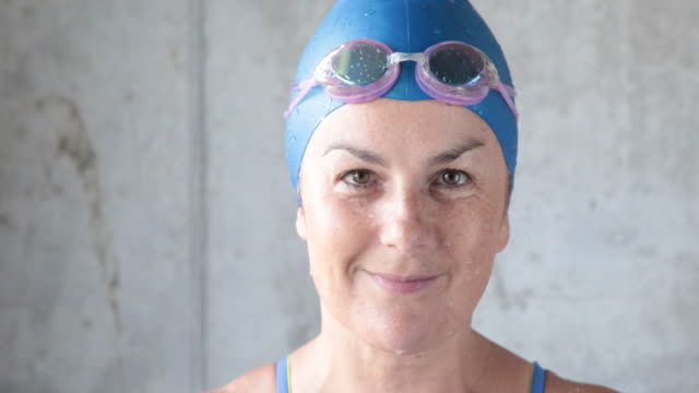 Mature female swimmer looks to camera smiling and puts on goggles
