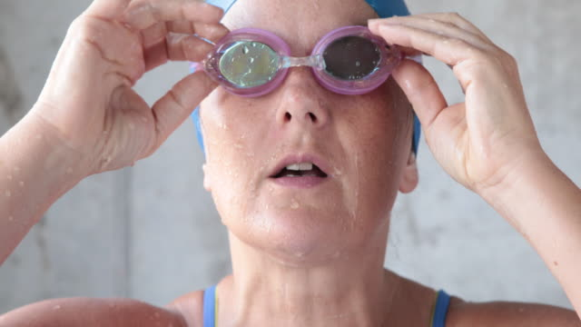 Mature female swimmer looks to camera taking off goggles, breathing out.