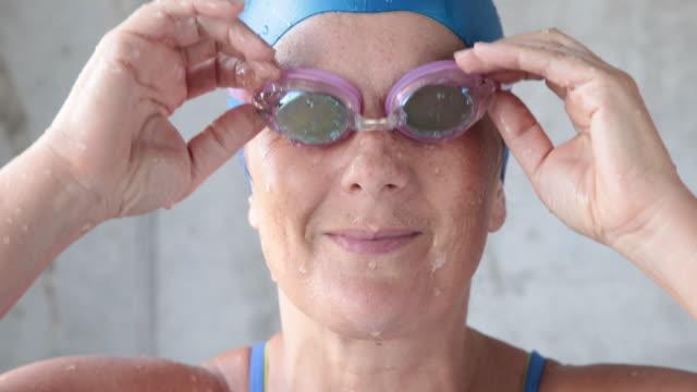 vídeos de stock e filmes b-roll de mature female swimmer looks to camera taking off goggles, smiling. - touca de natação