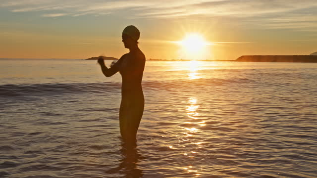 "mature female swimmer preparing for workout at sunrise - xavierarnau or ""xavier arnau serrat"" stock videos & royalty-free footage"