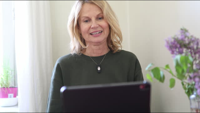 femmina matura che parla durante una videochiamata a casa - webcam video stock e b–roll