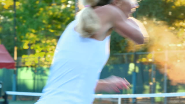 MS Mature female tennis player hitting return at net during early morning tennis match