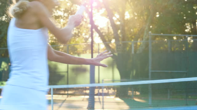 ms mature female tennis player hitting return at net during early morning tennis match - 60 64 years stock videos & royalty-free footage