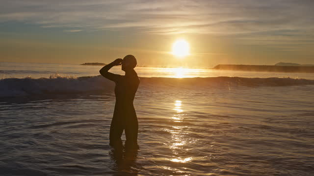 "mature female triathlete preparing for swim at sunrise - xavierarnau or ""xavier arnau serrat"" stock videos & royalty-free footage"