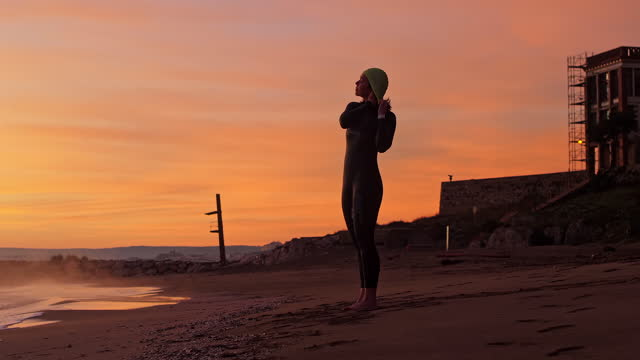 "mature female triathlete preparing for workout at dawn - xavierarnau or ""xavier arnau serrat"" stock videos & royalty-free footage"