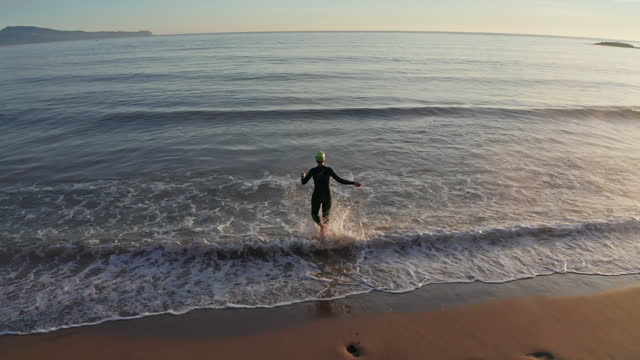 "mature female triathlete running into water for workout - xavierarnau or ""xavier arnau serrat"" stock videos & royalty-free footage"