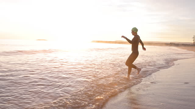 "mature female triathlete striding into mediterranean at dawn - xavierarnau or ""xavier arnau serrat"" stock videos & royalty-free footage"