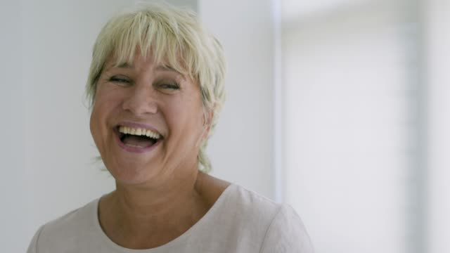 mature female woman laughing and smiling. - grey hair stock videos & royalty-free footage