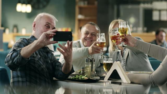 熟女のお友達がレストランで selfie を引き継ぐ - photo messaging点の映像素材/bロール
