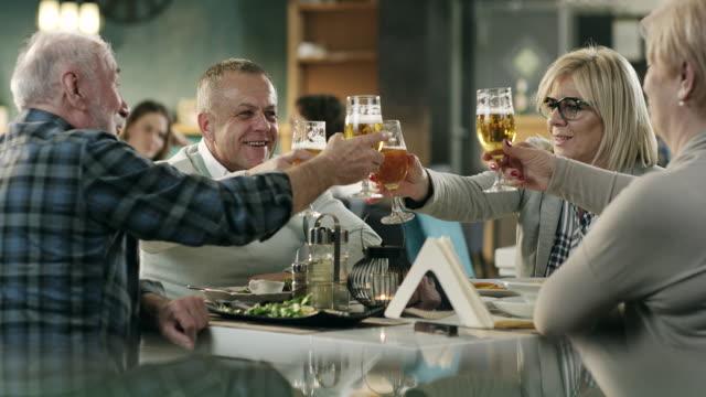 成熟した友達のレストランでビールを乾杯 - 食事する点の映像素材/bロール