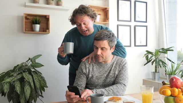 reife homosexuell paar essen frühstück und überprüfen nachrichten auf mobilen gerät - cereal plant stock-videos und b-roll-filmmaterial