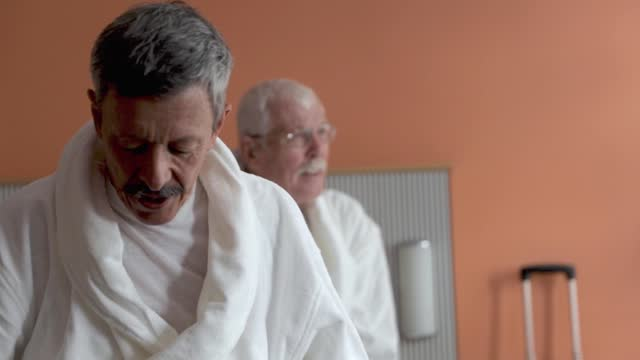 mature gay couple relaxing in bathrobes in hotel suite - handheld stock videos & royalty-free footage