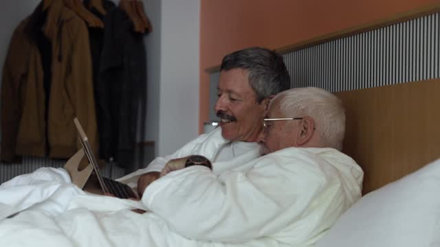mature gay couple watching film in bed together - bathrobe stock videos & royalty-free footage