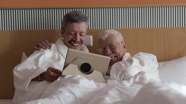 mature gay couple wearing bathrobes in hotel suite - sovrum bildbanksvideor och videomaterial från bakom kulisserna