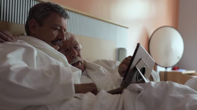 mature gay couple wearing bathrobes in hotel suite - bathrobe stock videos & royalty-free footage