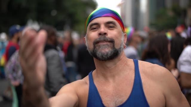 vídeos de stock, filmes e b-roll de homem gay maduro acenando na parada gay - homem homossexual