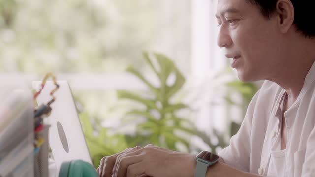 vídeos de stock e filmes b-roll de mature gay man talking to his partner at home while typing on laptop. - one mature man only