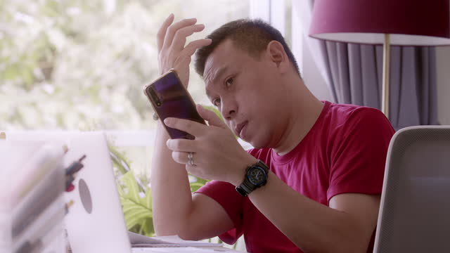 vídeos de stock e filmes b-roll de mature gay man using mobile phone as mirror. working from home. - one mature man only