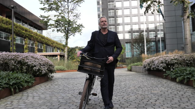 mature gray hair man riding bicycle and contributes to eco-friendly environment - netherlands stock videos & royalty-free footage