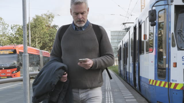 vídeos de stock e filmes b-roll de mature gray hair man using smart phone while commuting in autumn - homens adultos