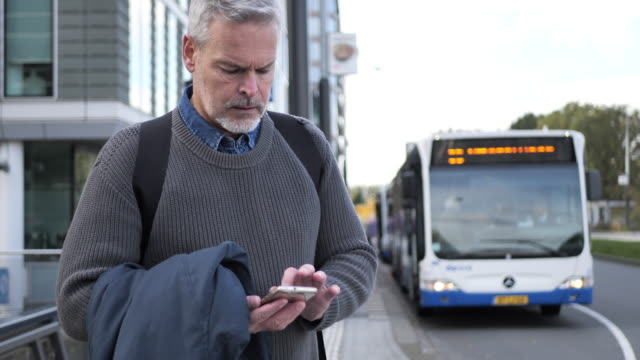 mature gray hair man using smart phone while commuting in autumn - mature men stock videos & royalty-free footage