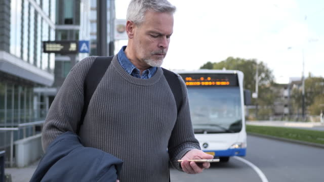 mature gray hair man using smart phone while commuting in autumn - rush hour stock videos & royalty-free footage