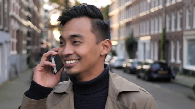 mature handsome asian businessman using mobile phone for talking - netherlands stock videos & royalty-free footage
