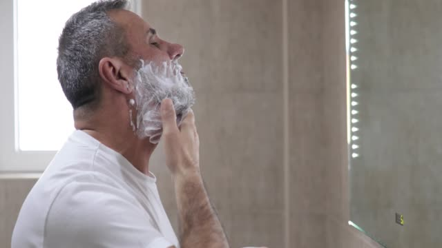 mature handsome man shaving in front of mirror - shaved stock videos & royalty-free footage