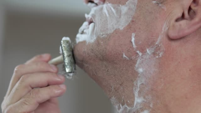 mature handsome man shaving in front of mirror - raso video stock e b–roll