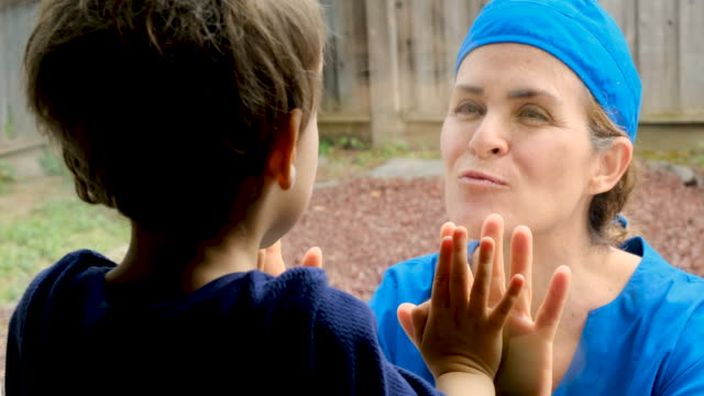 mature healthcare worker posing seeing her son with a window glass separating them to avoid possible contagion - love emotion stock videos & royalty-free footage