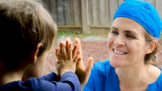 mature healthcare worker posing seeing her son with a window glass separating them to avoid possible contagion - nurse stock videos & royalty-free footage
