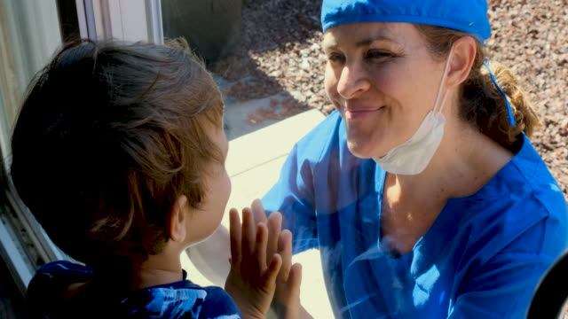 mature healthcare worker posing seeing her son with a window glass separating them to avoid possible contagion - son stock videos & royalty-free footage