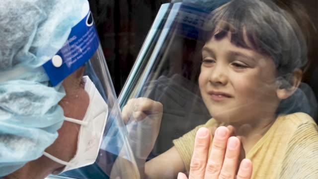 operatore sanitario maturo in posa vedendo suo figlio con un vetro della finestra che li separa per evitare possibili contagi - divisione video stock e b–roll