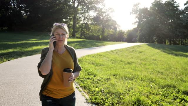 vidéos et rushes de femme en bonne santé mûre à l'extérieur le jour de ressort dans le stationnement utilisant le téléphone et parlant - parc naturel