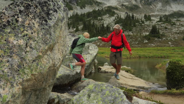 mature hiking couple enjoy high alpine boulder field and lake - boulder stock videos & royalty-free footage