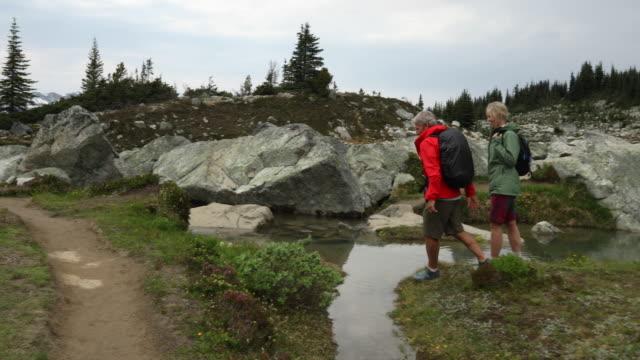 mature hiking couple enjoy high alpine boulder field and lake - boulder rock stock videos & royalty-free footage