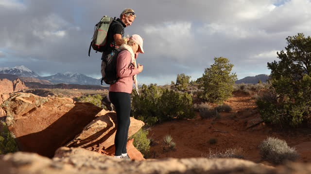 mature hiking couple relax, then leave resting rock - moab utah stock videos & royalty-free footage
