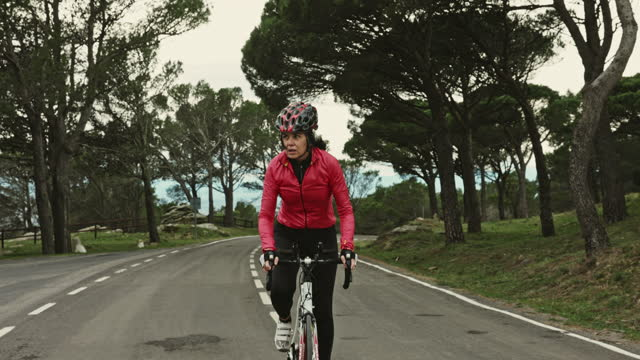 "mature hispanic female cyclist riding uphill on coastal road - xavierarnau or ""xavier arnau serrat"" stock videos & royalty-free footage"