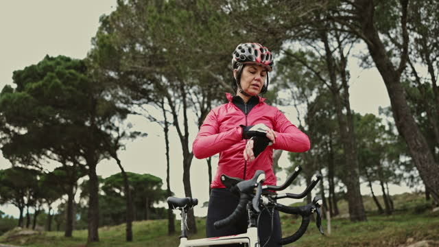 "mature hispanic female cyclist taking a break during workout - xavierarnau or ""xavier arnau serrat"" stock videos & royalty-free footage"