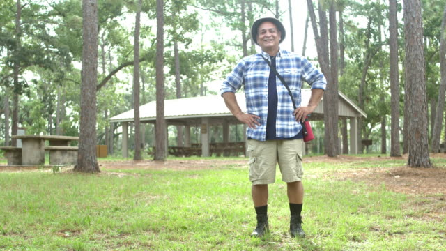 mature hispanic man going on a hike in the park - plaid shirt stock videos & royalty-free footage