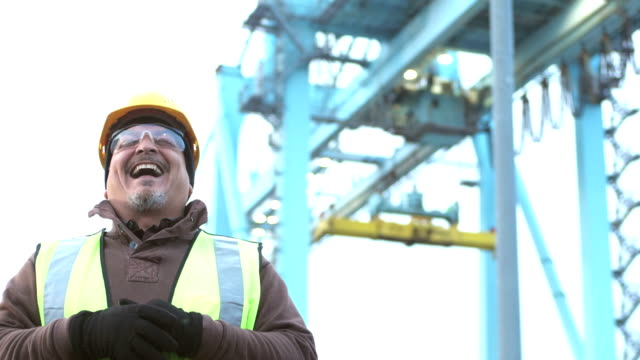 Mature Hispanic man working at seaport, laughing
